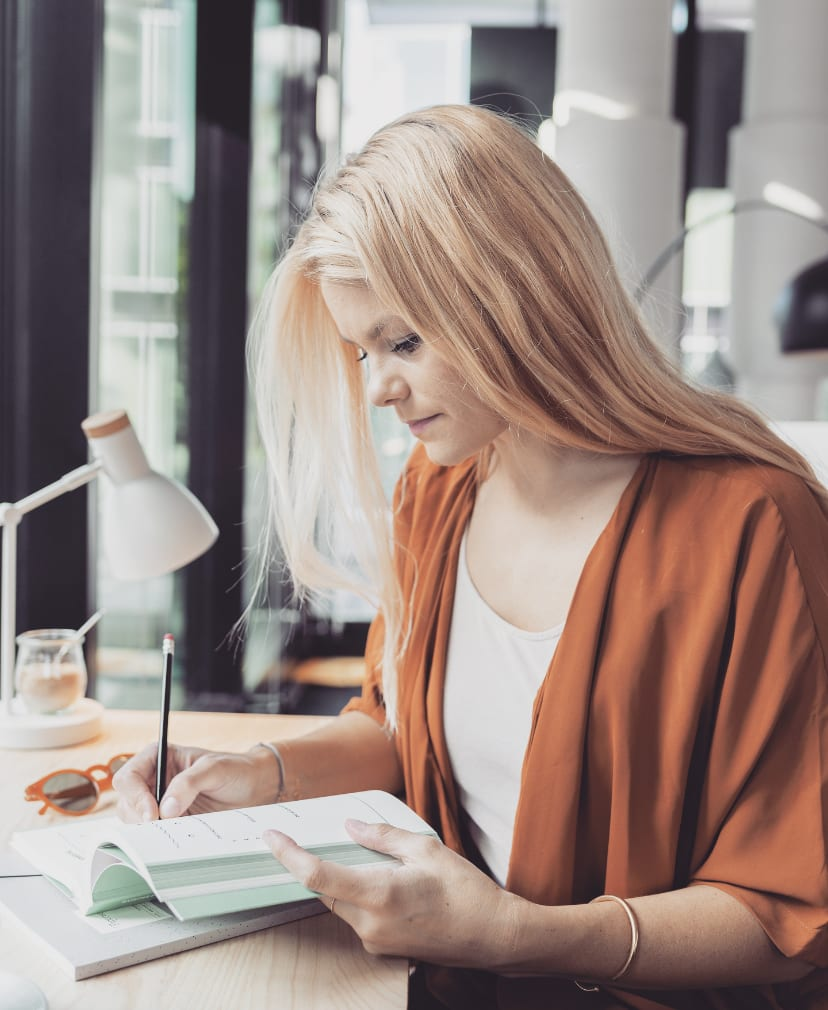 Blonde Frau sitzt im Café und schreibt an ihren Zielen in ein Notizbuch