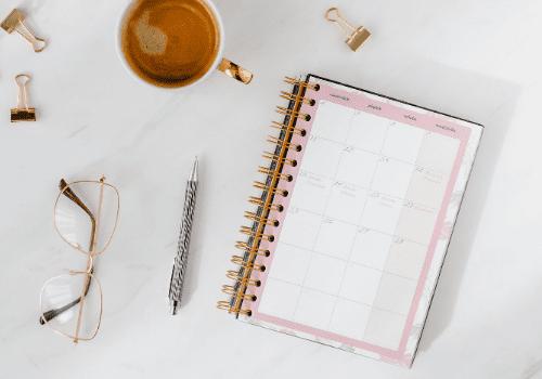 Notizbuch auf einem Tisch mit Kaffee, einer Brille und einem Stift
