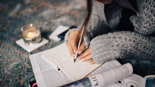 Frau zeichnet bei Kerzenschein und gemütlicher Atmosphäre etwas ins Business Journal
