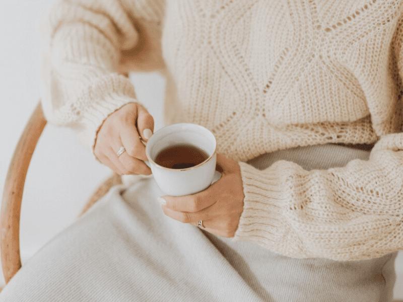 Frau mit cremefarbenen Kuschelpullover sitzt im Sessel und hält Teetasse in der Hand