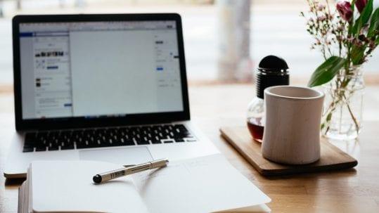 Buch und Laptop in einer Arbeitssituation im Büro